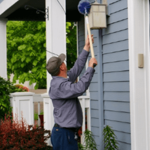 Croach - Home Pest Control - Beaverton, OR - Removing wasp nest from siding
